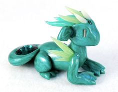 * Emerald dragon represents May in my Birthstone Collection - collect all 12! * Handmade dragon figurine is crafted from high quality colored polymer clay, sealed with a gloss glaze * Gems are genuine Swarovski crystal * Approximately 3 inches (8cm) long * Signed, dated original * Made to order item - 1-2 week turnaround time  This dragon represents May in my birthstone collection. Mays birthstone is emerald, so this dragon carefully guards a deep green glass rhinestone gem in his tail. In…