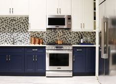 """The Signature Kitchen Suite Smart Kitchen is outfitted with navy and ivory cabinets by Green Forest Cabinetry and a glass tile mosaic backsplash. For Fuller, who comes from a product design background, the """"smart thinking"""" of the brand's designs put them ahead of the curve. For example, the Gas Slide-In Oven Range above has an Easy Swivel Handle that is easier and safer to operate, and the capacious refrigerator benefits from a SmartSpace System ice dispenser that maximizes storage space."""