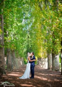 Bride and groom kissing in the plane tree walk, Fitzroy Gardens, Treasury Gardens
