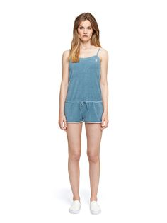 Blue women's short summer jumpsuit in baby terry (frotté) cotton. The 60's inspired jumpsuit has a thin strap top, drawstring waist, side pockets and white piping around side seams.