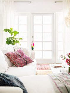 Pillows are a great way to incorporate pattern and color into an all white area | http://domino.com
