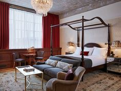 A stately four-poster anchors a guest room at Soho House Chicago.