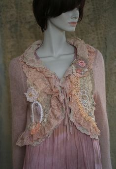 Feminine romantic reworked mohair jacket in shades of nude, cream, blush, is reworked with various antique and vintage laces appliques and beading. The delicate frothy collar is made of two layers of lace trims in ecry and blush, both hems are adorned with antique cotton lace details, ; at one side there is an image of ballerina in hand beaded frame of white seed beads. The sleeve ends are trimmed with cream silk and blush lace, jacket fastens with knit ribbons. Comes with a brooch pin in…