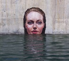 Riding atop a paddle board, artist Sean Yoro (aka Hula), paints murals while floating on the waves, placing his works just above sea level. The murals, all portraits of women, have a hyperrealistic quality that appear as if each is existing just above the tide. Due to the works' position above the w