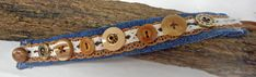 """This bracelet is 1"""" wide, with earth tone and antique brass buttons and findings on blue denim. It has a strip of ivory lace over pierced brown suede leather ribbon. It's 8"""" long, with a brown suede leather loop and brown vintage button closure."""
