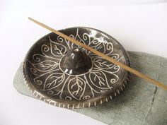 This pretty bowl ceramic incense holder is made from a white earthenware clay and black slip. A scrolling leaf design, inspired by Indian patterns, has been drawn through the slip to expose the white clay beneath - a technique called sgraffito. The pattern and upper surface is sealed under a transparent glaze. https://www.etsy.com/uk/listing/204453447/ceramic-pottery-incense-holder-ash