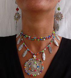 Questa bella collana era alluncinetto con cordone cerato beige/ecrù, perle di vetro, perle di metallo e piume dargento tibetane. Può essere
