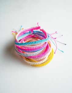 The best summer project around? Friendship bracelets... So portable, so cute and so easy! And you don't need to be intimidatingly crafty to make them. In fact, even if you have two left thumbs, these Breezy Friendship Bracelets are perfectly do-able.  Over the past few years, we have featured several knotted bracelet designs here on the Bee (click here to see them all), but this season's version is the easiest and breeziest. Made with two very simple knots, these bracelets work up so…
