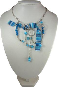 Dégradé de Bora Bora! La mer courtise le ciel! Collier bleu à longueur ajustable. Orné de pièces d'étain, de billes de verre et d'un magnifique ruban zébré. Une palette de bleus éclatants habite l'œuvre. Bijou bleu, collier fait au québec, collection Bora Bora Bijou de fantaisie