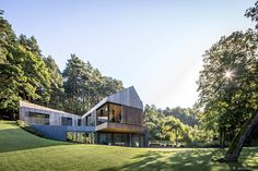 contrasting slate with timber, arches-designed valley villa cantilevers over a lithuanian hillside merging modern design with stringent zoning restrictions.