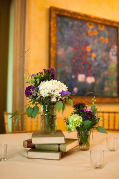 Centerpieces of stacked books & purple, ivory & green flowers   Feast at Round Hill Wedding With Color Of The Year Radiant Orchid Inspiration   Photograph by Matt Versweyveld  http://storyboardwedding.com/feast-at-round-hill-wedding-with-color-of-the-year-radiant-orchid-inspiration/