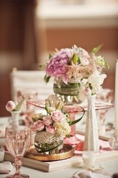 Mix-matched centrepieces - glass fish bowls with lace detail and white vases of various heights