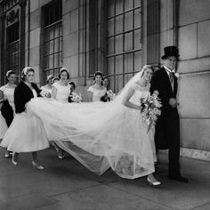 I LOVE this picture! A wedding party makes their way down the sidewalk in Manhattan, July 1956. #vintage #bride #groom #wedding #1950s
