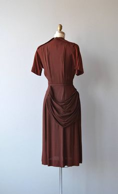 Vintage 1940s cocoa brown rayon crepe dress with small collar, V neckline, short sleeves, fitted waist, side metal zipper, matching belt and alluring hip and back drape. --- M E A S U R E M E N T S ---  fits like: extra small bust: 32-35 waist: 25.5 hip: 36 length: 45 brand/maker: Mary Muffet condition: very good, some color variation on shoulders  to ensure a good fit, please read the sizing guide: http://www.etsy.com/shop/DearGolden/policy  ✩ layaway is availab...