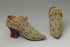 Pair of woman's tie shoes, 1720-1730, English, Linen with silk embroidery, silk ribbon, and leather. Yellow linen upper solidly embroidered with polychrome silk yarns in motif of plant in lozenge; latchets (with holes for tie) cross over high squared tongue; butted side and back seams; pink silk strips along top and over seams. Pointed toe. Red leather Louis heel. Brown leather sole. White leather welt. Brown leather insole, no lining.