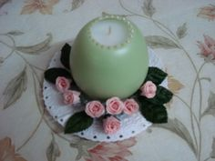 Hand poured white candle in a pastel green wax egg-shaped shell. Decorated with paper flowers and velvet leaves at the base