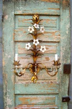 Antique door leaning against a wall w/a contrasting, elegant, sconce.