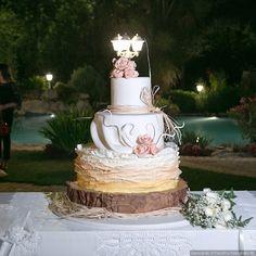 Ruffle cake per il matrimonio. Sottopiatto della torta con tronco e sfumature color pesca e rosa