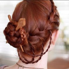 Viking inspired upstyle formed of a French braid with rope braid accents and carved wooden chopsticks
