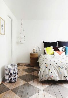 master bedroom // colorful bed pillows // polka dot duvet // white walls // diamond pattern wood floors