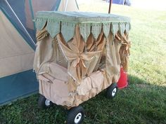 Radio Wagon Baby Palanquin. It sits on a radio flyer ATV wagon. Those are pockets all along the outside, with crib bumpers inside. back rest with seat belt. Creative design made by Christine Plummer