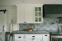 In addition to the new cabinetry and concrete countertops, we installed a bold patterned backsplash and a unique vent hood which was actually made out of wood. We hired a specialist to come in and paint it to look metal, which saved on budget and added a neat detail to the space. I chose to add this mobile wooden island to the kitchen to break up the black and white, and add some extra functionality to the room.