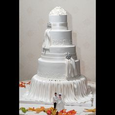 Palermo's White on White Draped Fondant Wedding Cake. The elegant draping in pearlized fondant transforms this simple white on white elegant wedding cake into a stunning cake table centerpiece. The cake jewelry adds sparkle, and the traditional cake topper placed in front adds a touch of retro charm.  This tiered cake is covered in pearlized fondant, decorated with swirled floral details, cake jewelry, and gumpaste flowers. It features elegant white pearlized fondant draping.