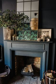 A gorgeous dark and moody, eclectic and glamorous living room design from Fiona Duke interiors with lovely copper framed mirror, botanical, tropical style influences and great fireplace styling.
