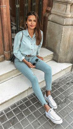 8 ideias de looks com camisa jeans para você testar. Calça skinny jeans clara com rasgo no joelho, tênis branco.
