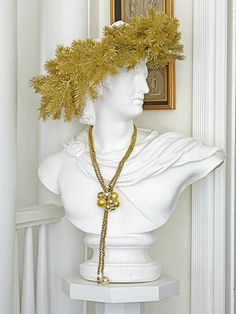 A wreath formed from a gold garland gives this bust a festive look. via  @Country Living Magazine by the fab @Eddie Ross