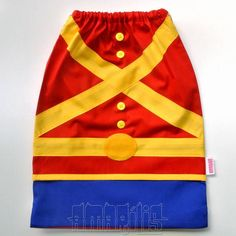"""CRIAÇÃO POR AMARÍLIS ATELIER! <br> <br>Mochila Infantil tipo """"Saquinho"""" no Modelo Soldadinho de Chumbo <br> <br>Tecido 100% Algodão! <br>Fechamento Prático! <br> <br>Blusa Vermelha com Barra Amarela <br>Calça Azul Royal <br>Faixas e Cinto Amarelos <br>Fivela do Cinto Amarela <br>Cadarço Branco <br> <br>Ideal para Lembranças de Aniversário! <br>Seus convidados vão adorar! <br> <br>PEDIDO MÍNIMO: 12 unidades <br>DIMENSÕES: 34 cm x 24 cm"""