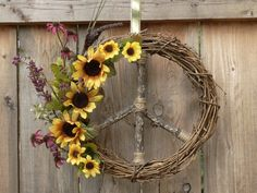 Here is a really pretty combination of vibrant gold and deep purple mini sunflowers along with a smoky purple catty-nine tail. For me this is a style that evokes that warm feeling of Autumn or late Summer. I really like the wood on this wreath, it has such cool characteristics, as only Mother Nature could design..awesome!  These Peace Sign Wreaths make wonderful gifts..Housewarming, Teen Room, College Dorm or Just Because!! This will be wonderful on a door, wall or mirror. This wreath makes…