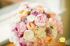 Wedding bouquet with pinks, peach, cream, purple, lavender colors.