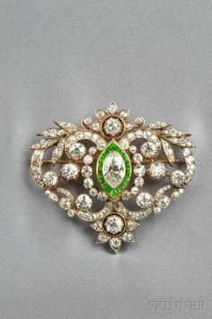 Edwardian Demantoid Garnet and Diamond Brooch, bezel-set with a marquise-cut diamond weighing approx. 1.75 cts., further set with old European- and old mine-cut diamonds, approx. total diamond wt. 9.50 cts., fancy-cut demantoid garnet accents, silver mount, lg. 2 1/8 in.