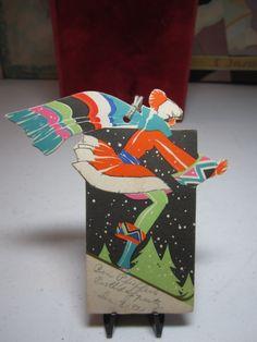 Colorful art deco die cut 1931 Buzza christmas bridge tally card deco lady downhill skiing in elaborate  and matching big scarf by puffadonna on Etsy https://www.etsy.com/listing/255027457/colorful-art-deco-die-cut-1931-buzza
