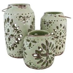 """Crafted from ceramic and showcasing a weathered green finish, this set of openwork candle lanterns adds a classic touch to your entryway console table or living room mantel.  Product: Small, medium and large candle lanternConstruction Material: CeramicColor: Weathered greenFeatures:  Distressed finishCut-out accentsAccommodates: (1) Candle - not includedDimensions: Small: 6.5"""" H x 6"""" DiameterMedium: 9.5"""" H x 5.5"""" DiameterLarge: 11.5"""" H x 6.5"""" Diameter"""