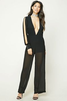 A semi-sheer woven jumpsuit featuring a plunging V-neck, long vented sleeves with button cuffs, back button closure, a keyhole cutout back, wide legs, and an invisible back zipper.