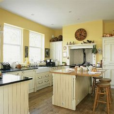 Cheery yellow country kitchen. Like the reclaimed wood floors, panelling on island, and apron front sink.