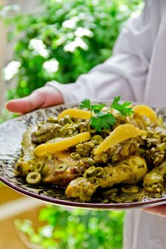 Chicken Lemon Tagine– 2 chicken , 1200g each, cut into 8 parts  – 1/2 cup parsley leaves, finelly chopped  – 1/2 cup cilantro leaves, finelly chopped  –  6 garlic cloves, diced  – 1 tsp ginger ground , powdered  – 1 tsp turmeric  – 1/2 tsp Moroccan Mroozya spices  – 1.2 tsp pepper ground  – 1 tsp salt  – 1g saffron  –  4 tbs lemon juice  –  1/4 cup olive oil  –  1 pickled lemon, sliced  – 1/2 pickled lemon, chopped  – 1/2 cup green olives  – 3 onions, chopped