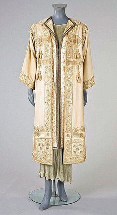 Description: A Maison Worth ivory wool coat, circa 1905-10, woven signature label applied to neck, with elaborate white and cream soutache braid and sinuous raised whitework embroidery. Front