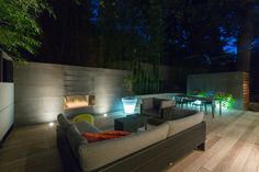 Modern Ipe deck lounge with Dedon outdoor furniture, stainless steel linear Bio-ethanol burner by BioFlame, Europhase in floor up lights, Viroc concrete walls, and wood slat wall at night and glowing planters in Washington DC. Wood Slat Wall, Wood Slats, Outside Living, Outdoor Living, Backyard, Patio, Outdoor Furniture Sets, Outdoor Decor, Outdoor Gardens