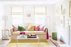 The beautiful design work of McGrath II--light, bright living room with white walls, cream sofa, colorful throw pillows, lucite coffee table and a perfect reading lamp.
