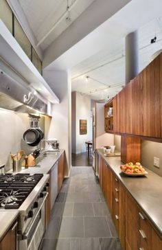 "classic galley kitchen, including the use of hanging pots and pans and commercial feel feel with the range hood. The super-efficient pattern of working left to right and right to left between sink and range is what I think of when I think ""galley kitchen."""