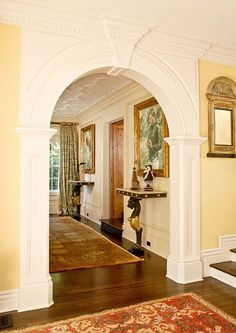 An elegantly trimmed arch connects the grand foyer with the living room. - Traditional Home ®/ Photo: Mark Edward Harris and Michael McCreary / Design: Timothy Corrigan