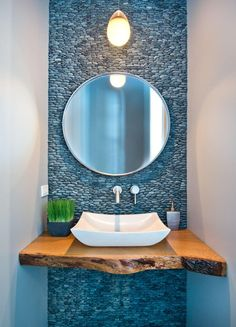 The wood element seems to anchor and balance the floating elements (the mirror and the light).