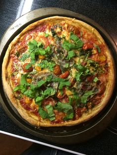 Arugula, pancetta, tomato, with sweetened tomato sauce. Making pizza at home is the best. Crust from scratch in Meatless cookbook.