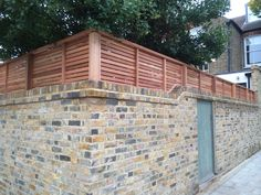 Slatted Cedar Fencing On Top Of Brick Wall Fence