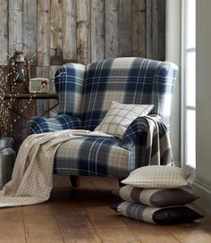 There is something oddly appealing and cozy about a tartan chair (<3 the tiny radio and pussywillows too). I would add a leather ottoman and change the pillows to something softer, maybe floral instead of checks or stripes?