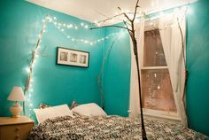 wall decor ideas, room with turquoise walls, and a white ceiling, lit string lights suspended from four dry tree branches, placed around a double bed