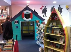 """I like the playfullness of this book corner, from the wall silhoettes to the rowing boat shelves - but the little beach hut open on just one side offers the privacy and visibility that seems to work so well - children within the """"hut"""" are in the big learning space, but also in a more initimate """"together"""" space"""